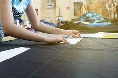 Tailor working with a cutting material in a workshop at a garment factory. Rostov, Russia - January 25: A beautiful young girl tailor working with a cutting royalty free stock images