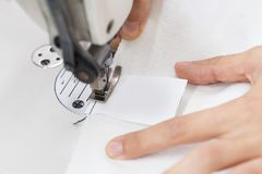 Tailor is working. Dress sews in the labelon sewing machine stock photography