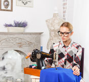 Tailor working in the fashion atelier. Using retro sewing machine Stock Photography