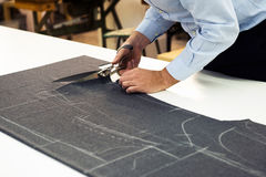 Tailor working in his shop cutting fabric Stock Photo
