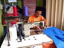A tailor works on a dress with his sewing machine Stock Photos