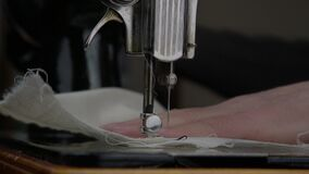 Tailor works on sewing machine and needle makes movements