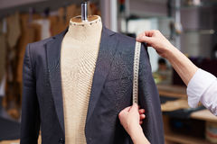 Tailored Suit in Atelier. Closeup of tailors hands measuring jacket with tape fitting bespoke suit Stock Image