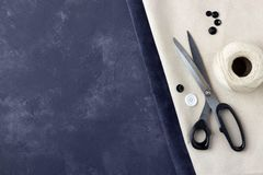 Tailoring concept - sewing accessories on dark blue and beije leather background royalty free stock photo