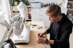 Fashion designer with making dress at studio Stock Photos