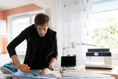Fashion designer cutting fabric at studio Royalty Free Stock Photos