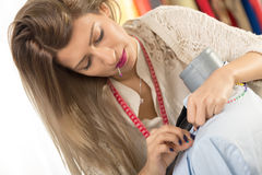 Tailoring With Straight Pin. Young beautiful woman with a sewing tape measure draped over the neck and straight pin in her mouth, tailor clothes on a mannequin Stock Image