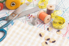 Tailoring tools. Sewing items background with old scissors, thread spools and tape measure Stock Photos