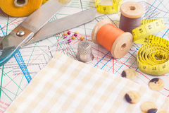 Tailoring tools. Sewing items background with old scissors, thread spools and tape measure Royalty Free Stock Image