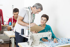 Tailors Discussing Over Clipboard In Sewing Factory. Male and female tailors discussing over clipboard at workbench in sewing factory Royalty Free Stock Photography