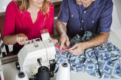 Tailors Discussing At Workbench In Factory. High angle view of male and female tailors discussing at workbench in sewing factory Royalty Free Stock Images