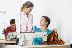 Tailors Discussing At Workbench In Factory. Smiling female tailors discussing at workbench in sewing factory Royalty Free Stock Photos