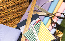 Tailors Scene. Brightly Colored Swatches in Wicker Basket with Wooden Rulers, Measuring Tape and Scissors Royalty Free Stock Photo