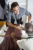 Tailors Shaking Hands At Workbench In Sewing Factory Royalty Free Stock Photo