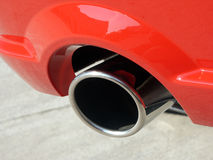 Tailpipe on new red sports car. Close up of tail pipe on red sports car showing a little of tire and ground Royalty Free Stock Photo