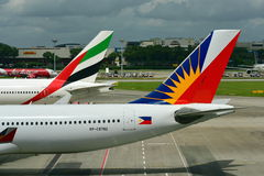 Tails of Emirate Boeing 777-300ER and Philippines Airlines Airbus 330 at Changi Airport Royalty Free Stock Photography