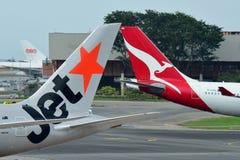 Tails of Jetstar International and Qantas aircraft belonging to the same family at Changi Airport Stock Photo