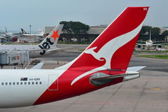 Tails of Jetstar International and Qantas aircraft belonging to the same family at Changi Airport Stock Image