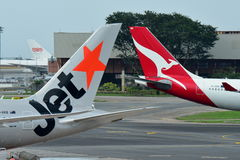 Tails of Jetstar International and Qantas aircraft belonging to the same family at Changi Airport Stock Images