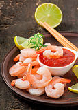 Tails of shrimps with fresh lemon and rosemary. In a ceramic plate Stock Photo