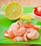 Tails of shrimps with fresh lemon and rosemary. In a green plate Royalty Free Stock Image