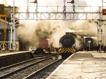 A steam train entering a station`s platform with billowing smoke stock image