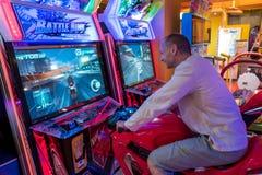 Tainan, Тайвань - 25-ое сентября 2018: Кавказский человек играя видеоигру всадника сражения в аркаде стоковая фотография rf