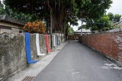 Tainan, Taiwan - November 24,2017: Wand des roten Backsteins und farbige Stühle Lizenzfreie Stockfotografie