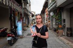 Tainan Taiwan - September 25, 2018: Blond flicka som rymmer den ensamma planetlopphandboken för Taiwan royaltyfri bild