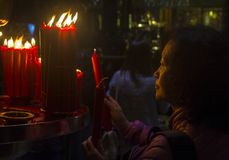 Taipei Longshan temple. TAIPEI - FEB 18 : Taiwanese woman lights a candle during Chinese new year in Longshan temple in Taipei Taiwan on February 18 2018. The Royalty Free Stock Photography