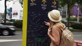 TAIPEI, TAIWÁN - 15 DE MAYO DE 2019: Mapa de exploración turístico femenino caucásico joven en la calle Viaje a solas Mujer encen almacen de metraje de vídeo