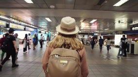 TAIPEI, TAIWÁN - 15 DE MAYO DE 2019: Turista femenino caucásico joven que camina entre las muchedumbres de gente subterráneo en s metrajes