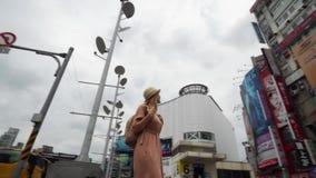 TAIPEI, TAIW?N - 15 DE MAYO DE 2019: Turista femenino cauc?sico joven que camina en ciudad grande en d?a nublado Viaje a solas metrajes
