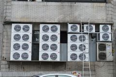 TAIPEI, TAIWAN - CIRCA March, 2018: Variety type of split unit air conditioner compressor. On the wall outside of industrial building royalty free stock photos