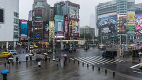 Time lapse of traffic and people walking on crosswalk with falling rain at Ximending in Taipei, Taiwan stock video