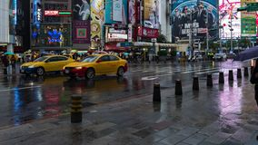 Time lapse of traffic and people walking on crosswalk with falling rain at Ximending in Taipei, Taiwan stock footage