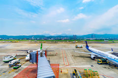 View of Songshan airport airplanes. TAIPEI, TAIWAN - JUNE 09: This is a view of the runway of Songshan airport with airplanes getting ready to board passengers Stock Photo
