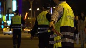 Slow motion police officer, regulates pedestrians used flashing light stick
