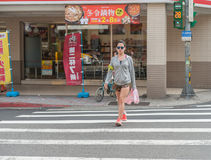 TAIPEI, TAIWAN - NOVEMBER 30, 2016: Taipei Street in one of suburb, district. Girl is Crossing the street. Taipei Street in one of suburb, district. Girl is Royalty Free Stock Photo