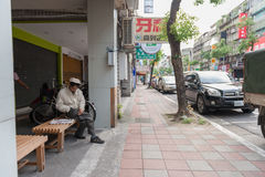 TAIPEI, TAIWAN - NOVEMBER 30, 2016: Taipei Street in one of suburb, district. People Sitting on the Bench. Taipei Street in one of suburb, district. People Royalty Free Stock Image