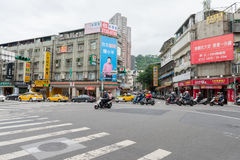 TAIPEI, TAIWAN - NOVEMBER 30, 2016: Taipei Street in one of suburb, district. Scooters Crossing the Street. Stock Image