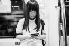 Taipei, Taiwan - October 01, 2018: A schoolgirl looking at her mobile phone in the Taipei MRT. stock photo