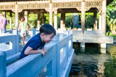 Taipei, Taiwan - September 19, 2018: Kid looking at fish in the garden of the Palace Museum. stock photos