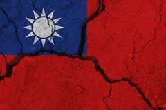 Taiwan flag on the cracked earth. National flag of Taiwan. Earthquake or drought concept royalty free stock photography