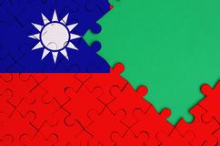 Taiwan flag is depicted on a completed jigsaw puzzle with free green copy space on the right side.  stock photo