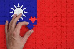 Taiwan flag is depicted on a puzzle, which the man`s hand completes to fold.  royalty free stock photo