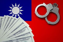 Taiwan flag with handcuffs and a bundle of dollars. The concept of illegal banking operations in US currency.  royalty free stock photography