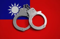 Taiwan flag and police handcuffs. The concept of observance of the law in the country and protection from crime.  royalty free stock image