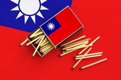 Taiwan flag is shown on an open matchbox, from which several matches fall and lies on a large flag.  royalty free stock image