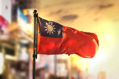 Taiwan flagga mot suddig bakgrund för stad på soluppgångpanelljuset Fotografering för Bildbyråer